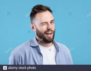 confident-handsome-caucasian-man-winking-and-smiling-at-camera-on-blue-studio-background-2DM1N0G.jpg